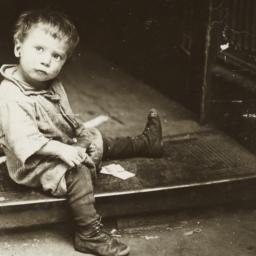 Boy Sitting on Grate