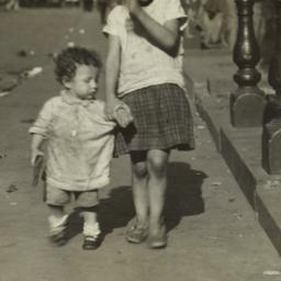 Girl Holding Hand of Small ...