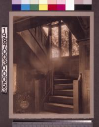 Entry hall staircase with stained glass window.