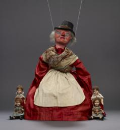 Female Marionette With Four Children In Her Pockets