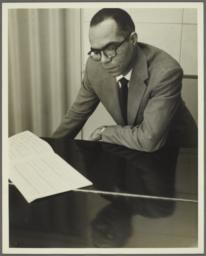 Ulysses Kay leaning on piano with manuscript